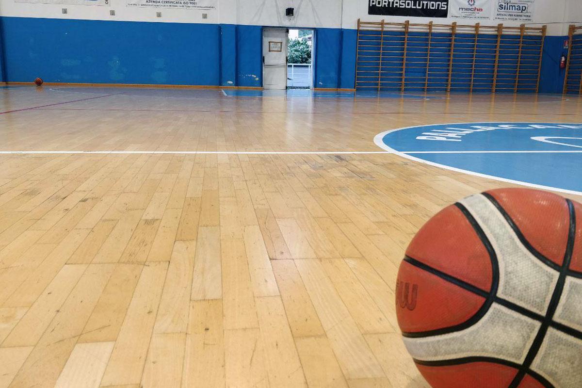 Pallone da basket in primo piano sul parquet del palazzetto